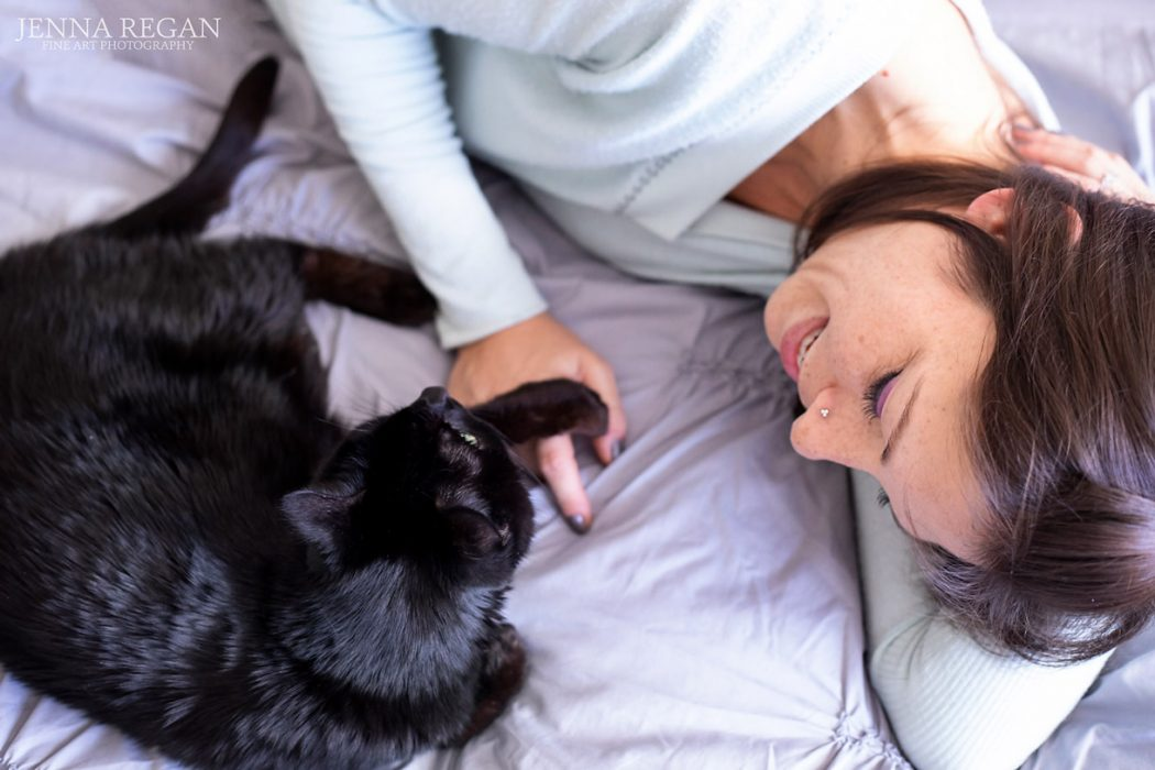 black cat laying on bed with owner showing bond during cat photography session