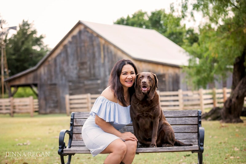 dog mom photographed on bench at park with senior chocolate lab in north texas- outdoor pet photo shoot