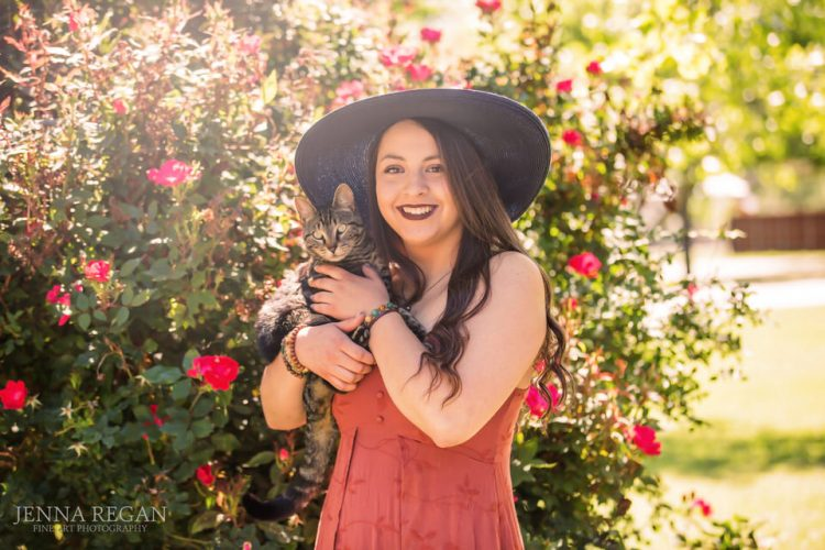 senior girl posing by roses with pet cat