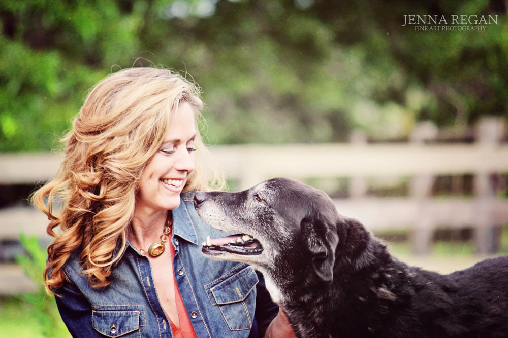 woman and dog bond during outdoor photo shoot