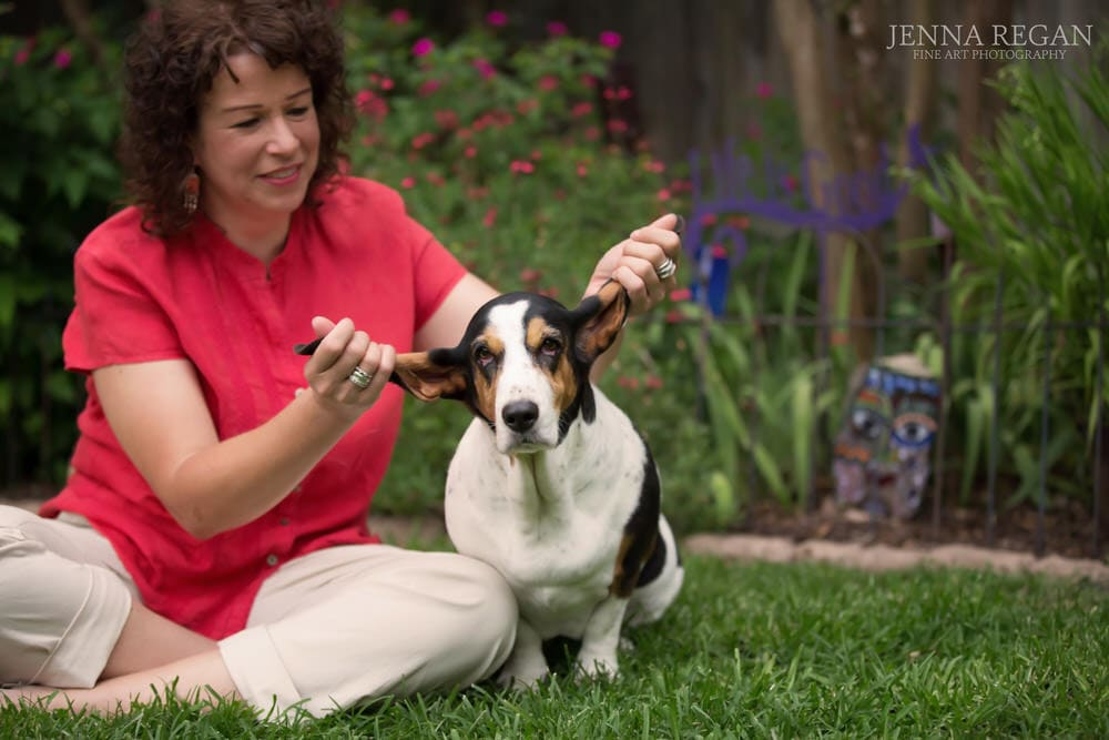 woman plays with basset hound in the grass in fort worth