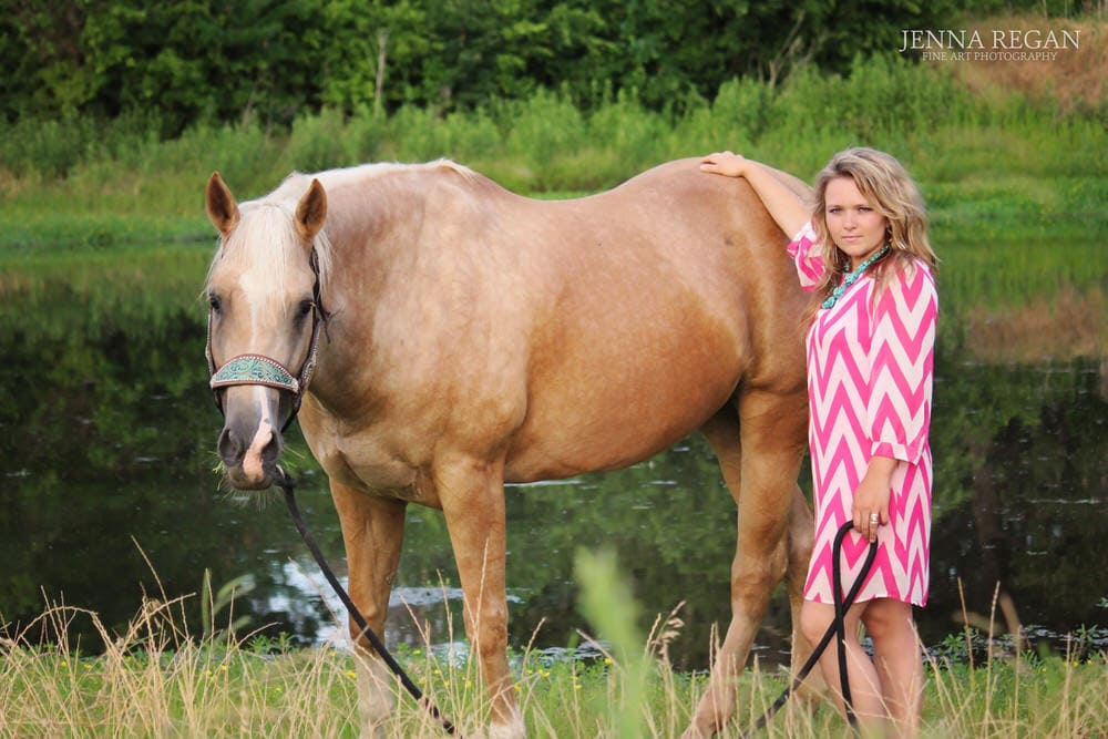 woman poses with her palomino horse by pond during photo session with jenna regan photography