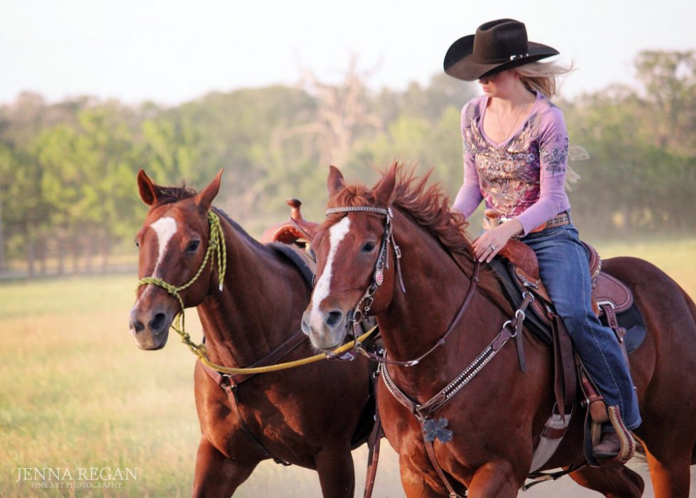 woman rides her barrel horse and ponies another horse during equine photo shoot