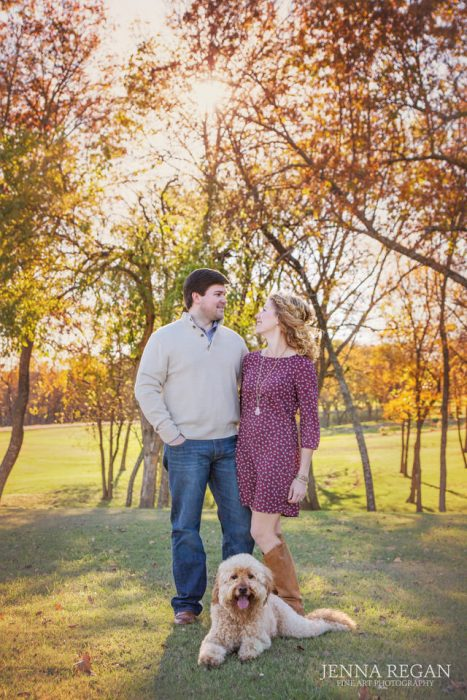 fall leaves young couple with their goldendoodle dog at sunset in texas park